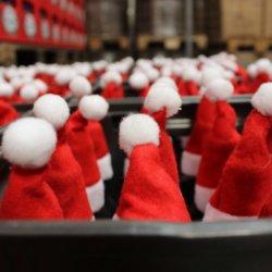 Weihnachtsmützen auf Bierflaschen bei der Produktion von Bier-Adventkalendern